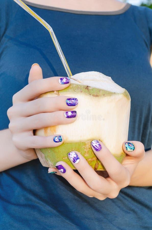 有拿着椰子的紫色指甲艺术贴纸的女性手 库存照片