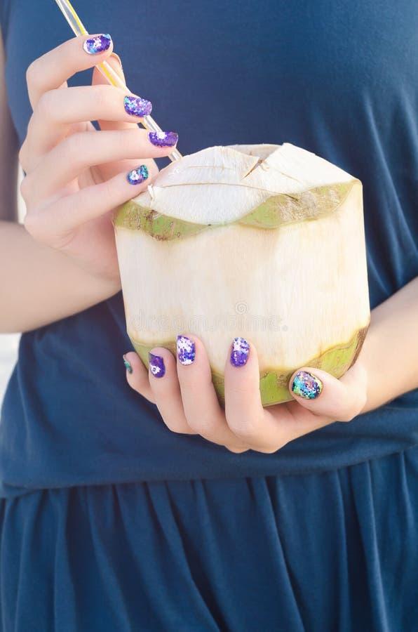 有拿着椰子的紫色指甲艺术贴纸的女性手 库存图片
