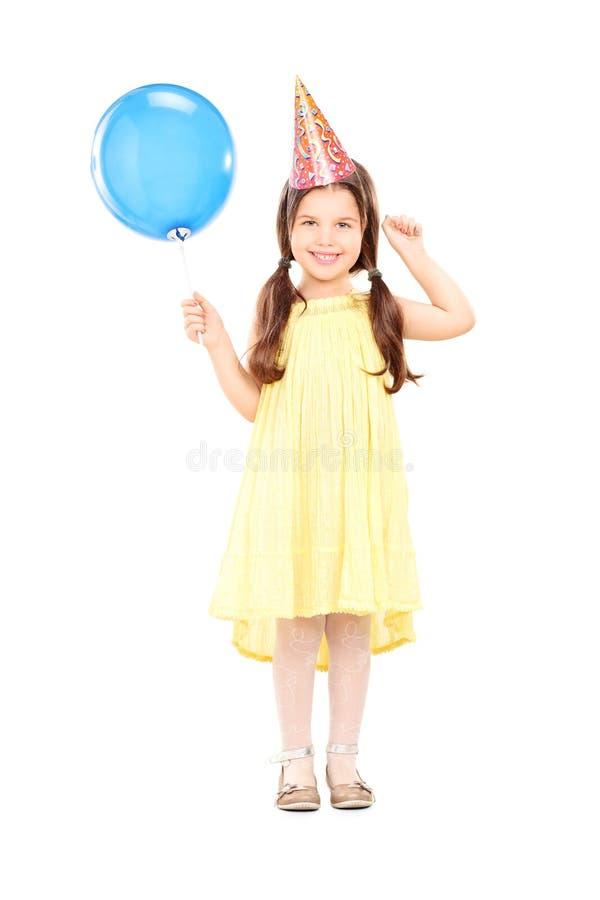 有拿着气球的党帽子的逗人喜爱的小女孩 库存图片