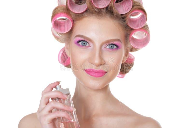 有拿着瓶香水的桃红色卷发夹的美丽的年轻女人 免版税库存图片