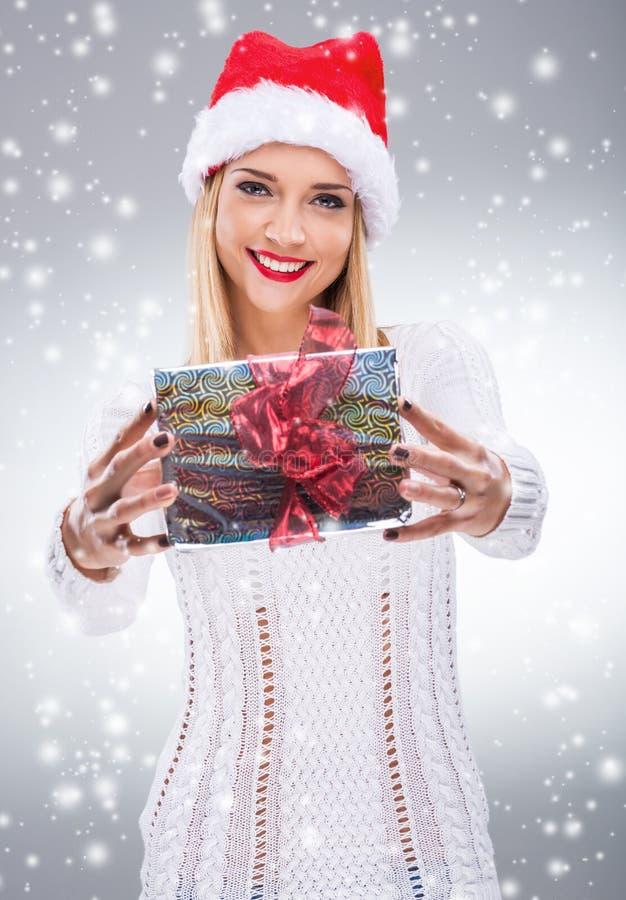 有拿着礼物的圣诞老人帽子的美丽的妇女对您 图库摄影