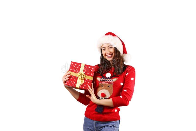 有拿着礼物的长的卷发佩带的圣诞老人项目帽子andd的年轻深色的妇女 免版税库存照片