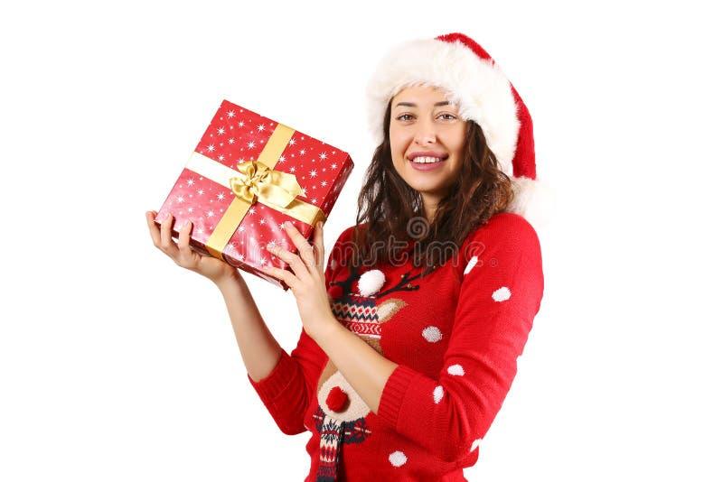 有拿着礼物的长的卷发佩带的圣诞老人项目帽子andd的年轻深色的妇女 库存照片