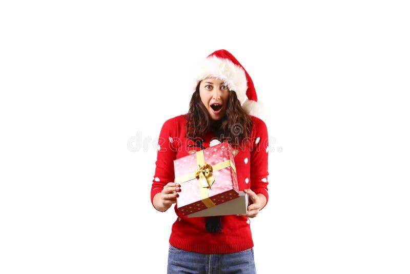 有拿着礼物的长的卷发佩带的圣诞老人项目帽子andd的年轻深色的妇女 库存图片