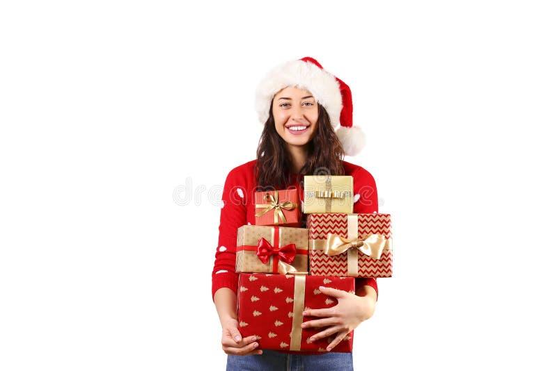 有拿着礼物的长的卷发佩带的圣诞老人项目帽子andd的年轻深色的妇女 免版税库存图片
