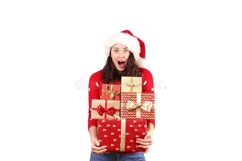 有拿着礼物的长的卷发佩带的圣诞老人项目帽子andd的年轻深色的妇女 图库摄影