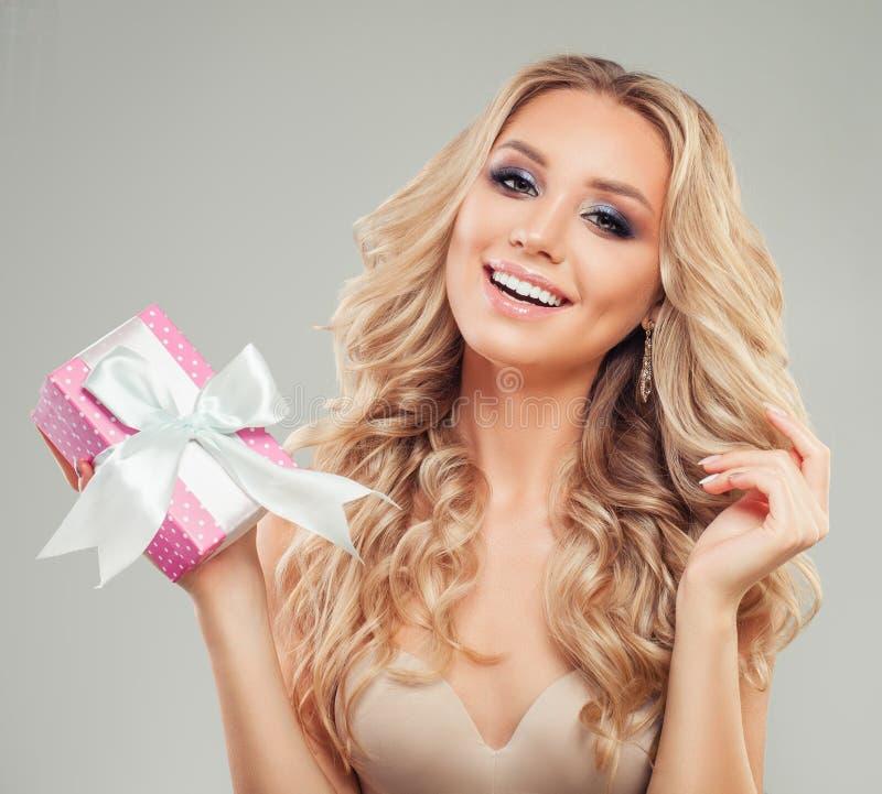 有拿着礼物盒的长的金发的愉快的惊奇的妇女 免版税库存图片