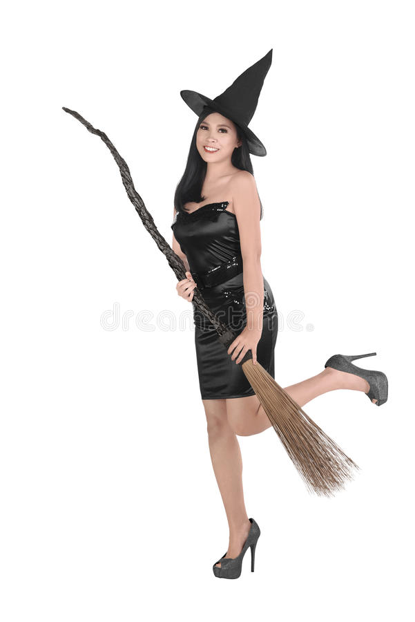 有拿着笤帚的帽子的美丽的亚裔巫婆妇女 库存图片