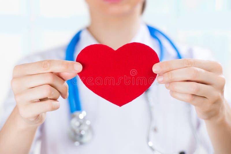 有拿着红色人的心脏的听诊器的女性医生 免版税库存照片