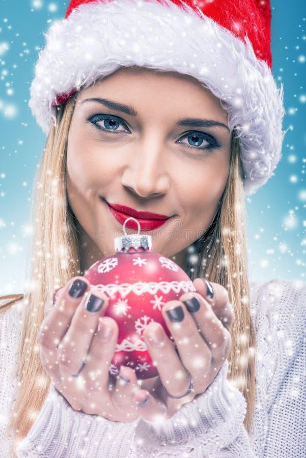 有拿着红色圣诞节装饰品-特写镜头的圣诞老人帽子的Â美丽的妇女 免版税库存图片