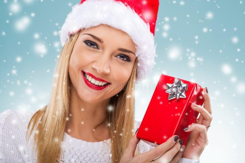 有拿着红色礼物盒,特写镜头的圣诞老人帽子的美丽的妇女 库存图片
