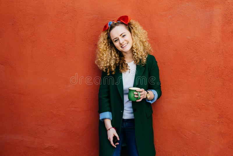 有拿着绿色咖啡的卷发佩带的头饰带和时髦的夹克的年轻时兴的白种人妇女有愉快的exp 免版税库存照片