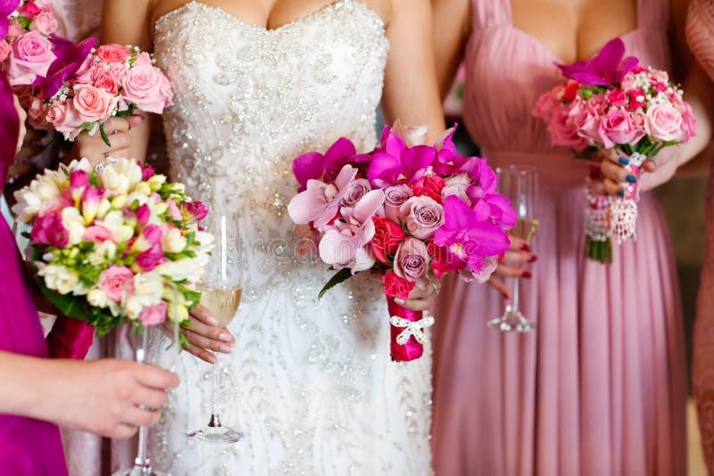 有拿着美丽的花的女傧相的新娘 库存照片