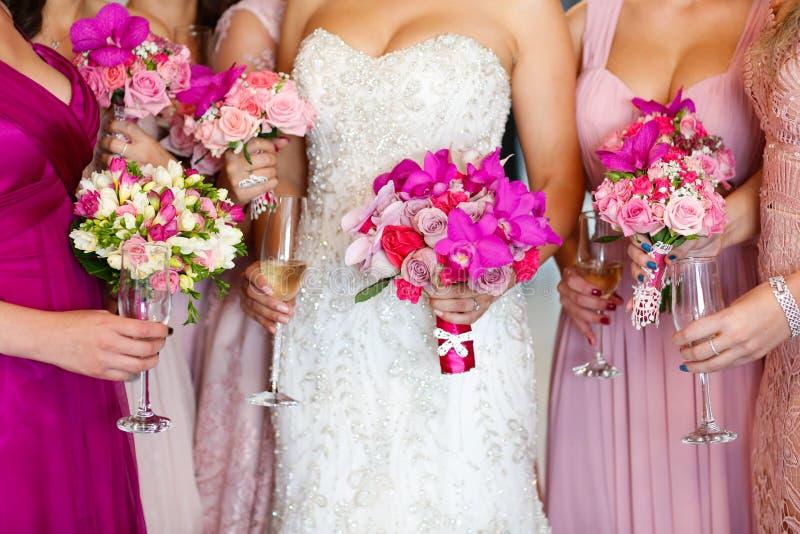 有拿着美丽的花花束的女傧相的新娘 库存图片