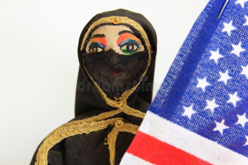 有拿着美国国旗的伯卡的阿拉伯玩偶 库存照片