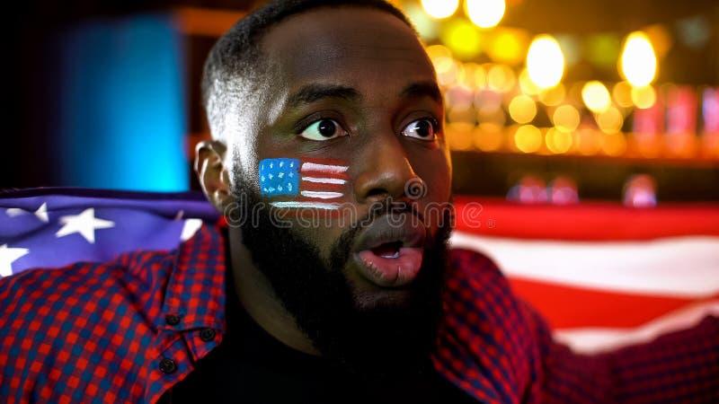 有拿着美国旗子,观看的棒球的被绘的面颊的震惊美国黑人的人 免版税库存照片