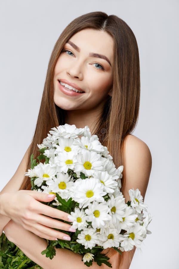 有拿着花的干净的新鲜的皮肤的美丽的妇女 免版税图库摄影