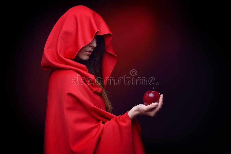 有拿着苹果的红色斗篷的美丽的妇女 免版税图库摄影