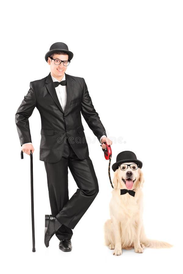 有拿着藤茎和狗的蝶形领结的魔术师 免版税库存图片