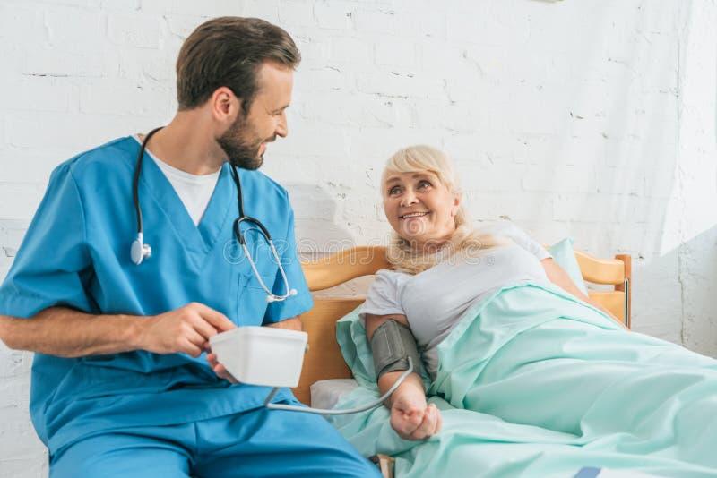 有拿着血压显示器的听诊器的微笑的男性护士,当测量血压对资深妇女时 库存图片