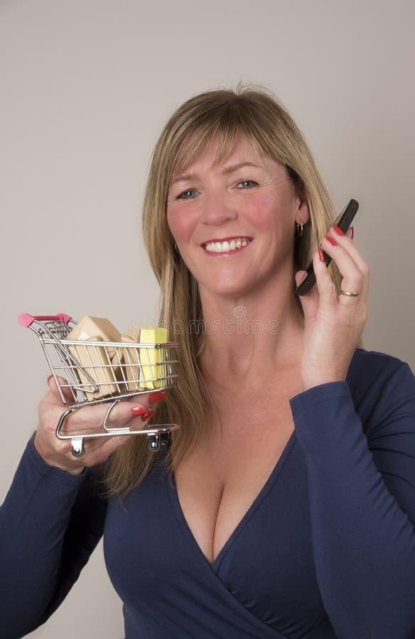 有拿着超级市场台车的电话的妇女 库存照片