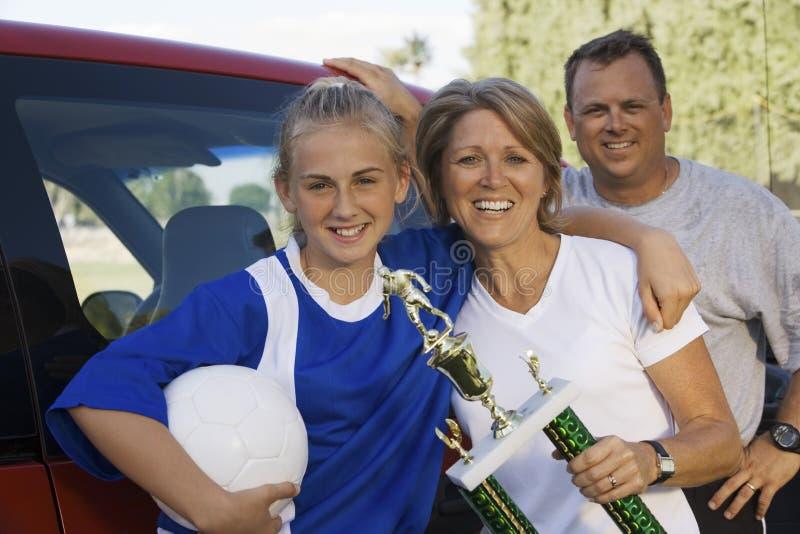 有拿着足球战利品的女儿的父母 免版税库存照片
