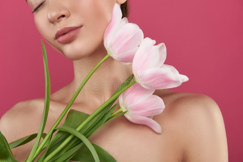 有拿着郁金香的充分的玫瑰色嘴唇的美丽的年轻女人 免版税库存图片