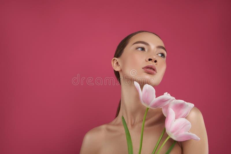 有拿着郁金香的赤裸肩膀的美丽的年轻女人 库存照片