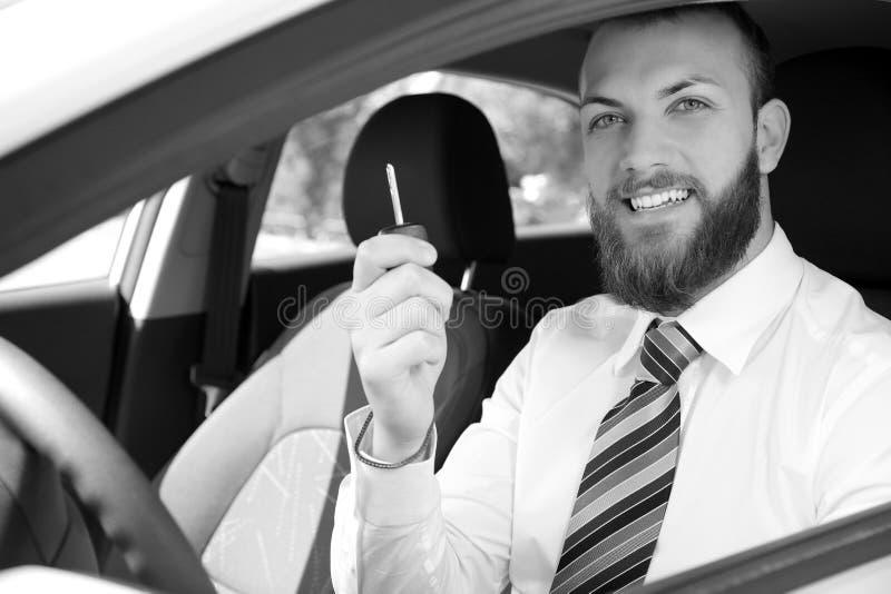 有拿着钥匙黑白画象的新的汽车的愉快的商人水平 库存图片