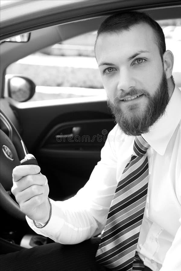 有拿着钥匙黑白画象的新的汽车的愉快的商人 库存照片