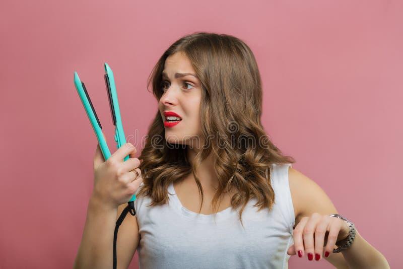 有拿着头发铁的一头波浪发的美丽的妇女 图库摄影