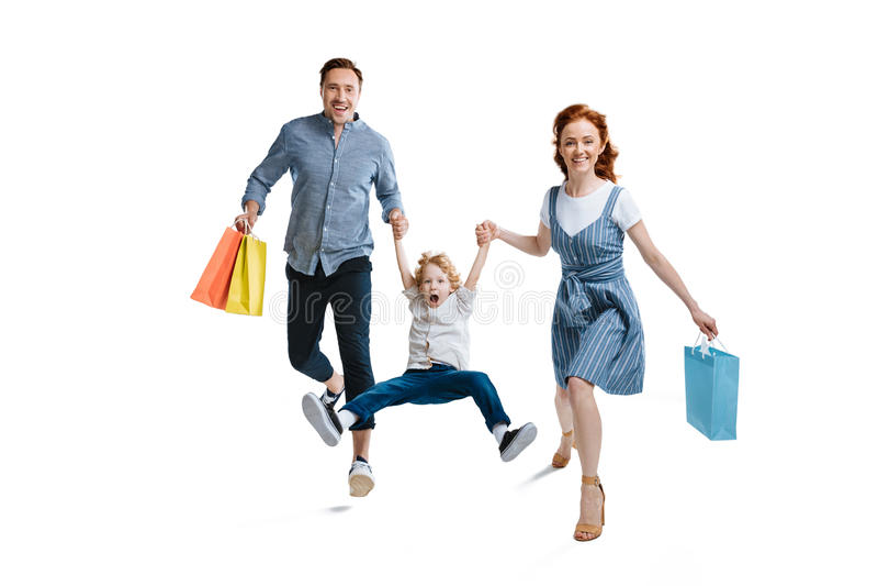 有拿着购物袋的一个孩子的愉快的年轻家庭 库存照片