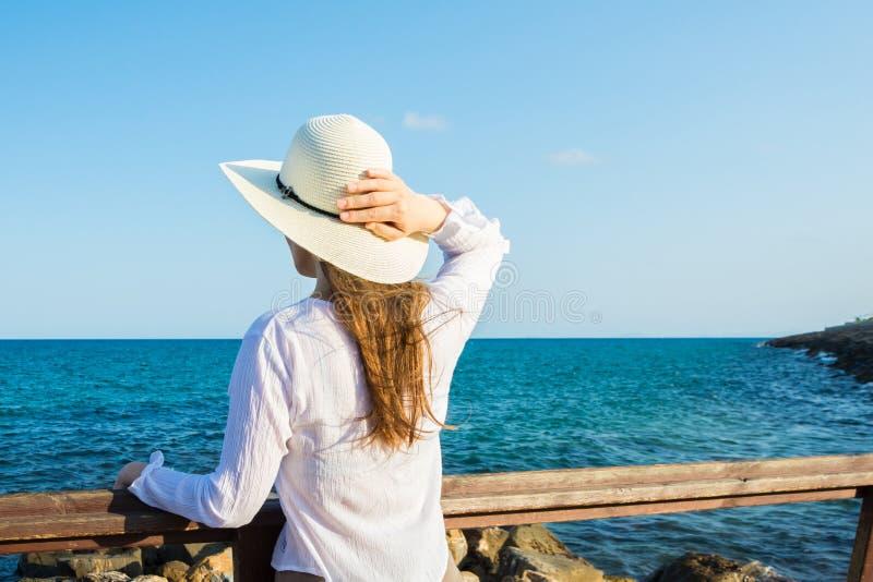 有拿着从风的长的头发的年轻美丽的苗条妇女sunhat在boho样式在岸看和海穿衣 库存图片