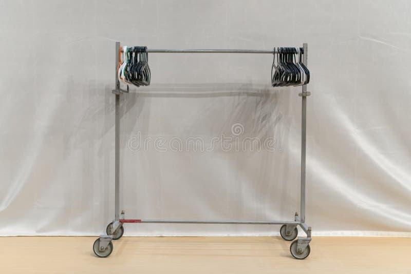 有挂衣架的基本的可调整的服装衣物机架 在白色隔绝的衣橱 与挂衣架的衣橱立场在轻的背景 免版税库存照片
