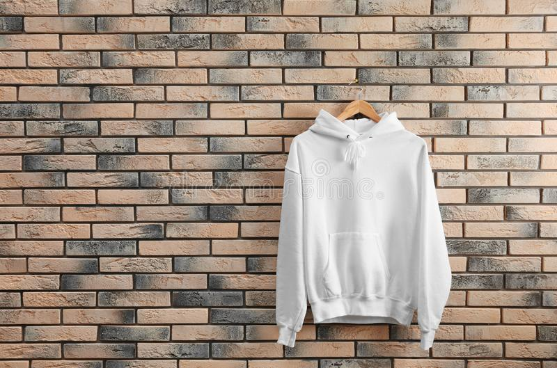 有挂衣架的新的有冠乌鸦毛线衣在砖墙上 免版税图库摄影