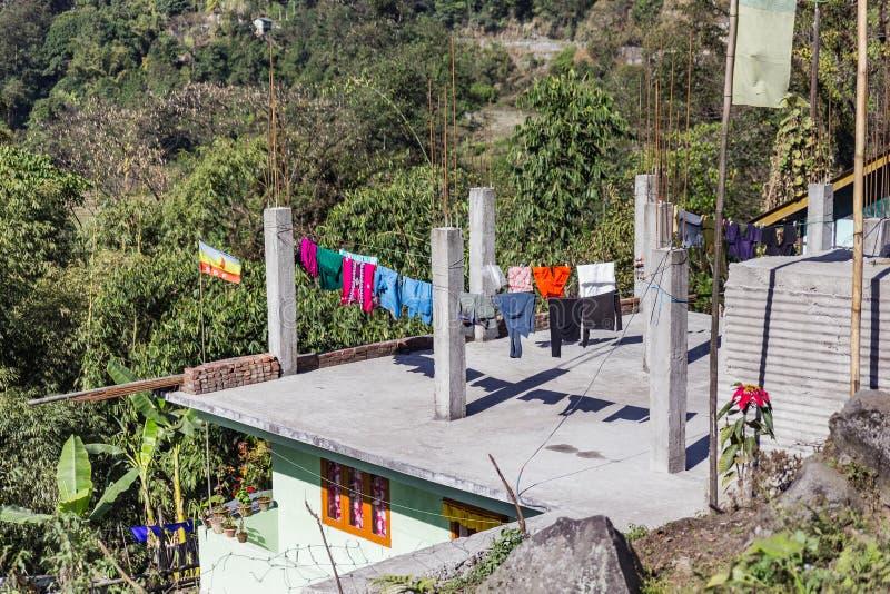 有挂衣架路轨的未完成的建造场所干燥衣裳的在阳光下在锡金,印度 库存图片