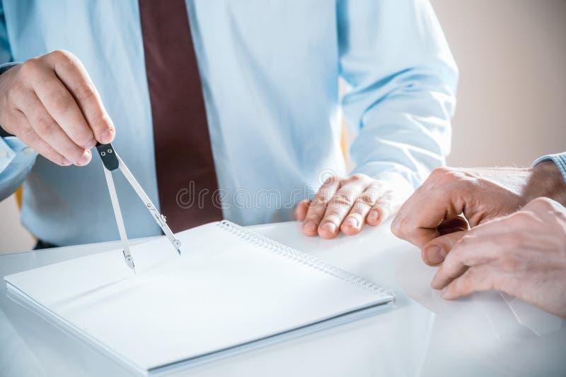 有指南针和笔记薄的建筑师在会议 免版税库存照片