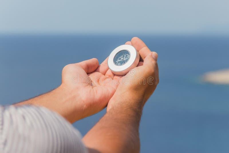 有指南针的手在蓝色海洋和天空背景 免版税库存照片