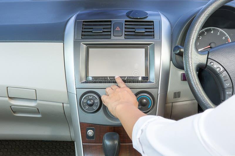 有按力量按钮的白色衬衣的女性手起动汽车收音机 免版税库存照片