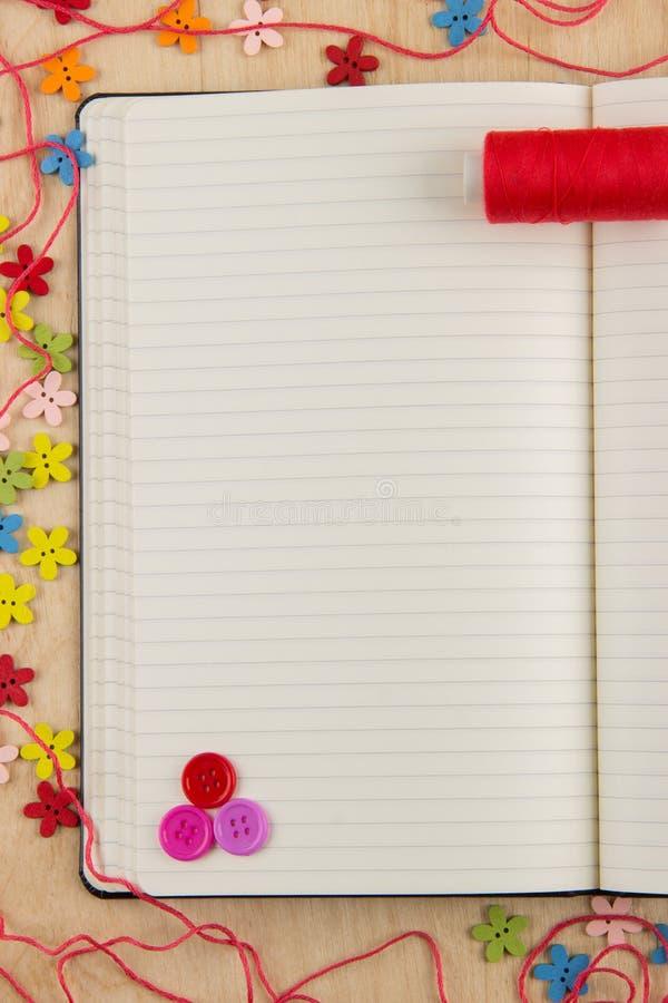 有按钮的开放笔记本页女裁缝,螺纹,花和 免版税库存照片