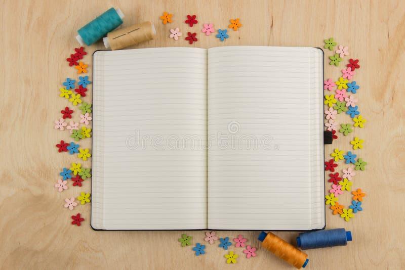 有按钮的开放笔记本页女裁缝,螺纹,花和 免版税库存图片