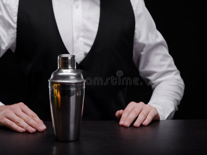 有振动器的侍酒者 一套衣服的专业男服务员与在黑背景的一台振动器 鸡尾酒准备概念 库存图片