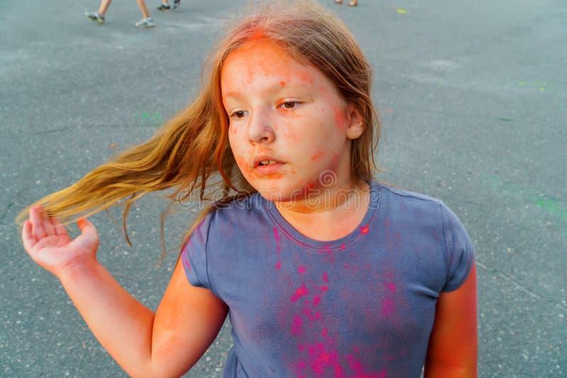 有振翼的头发的可爱的女孩盖了五颜六色的油漆在侯丽节节日 库存照片