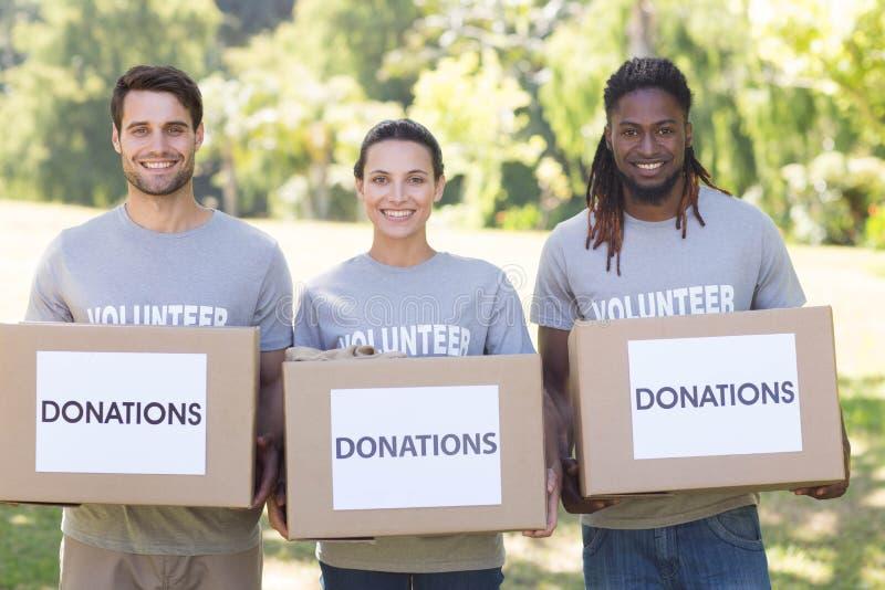 有捐赠箱子的愉快的志愿者在公园 库存图片