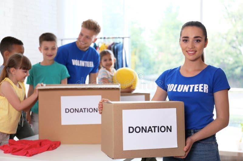 有排序捐赠物品的孩子的志愿者 免版税库存照片