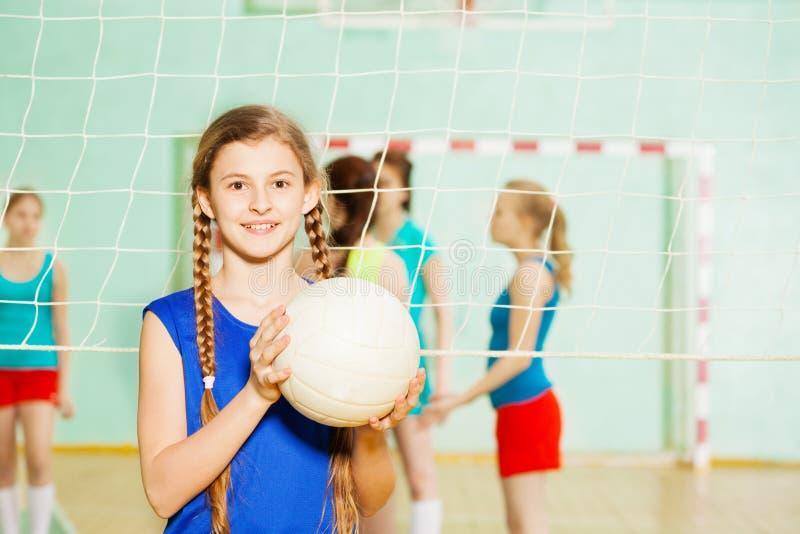 有排球球的青少年的女孩在体育馆里 免版税库存照片