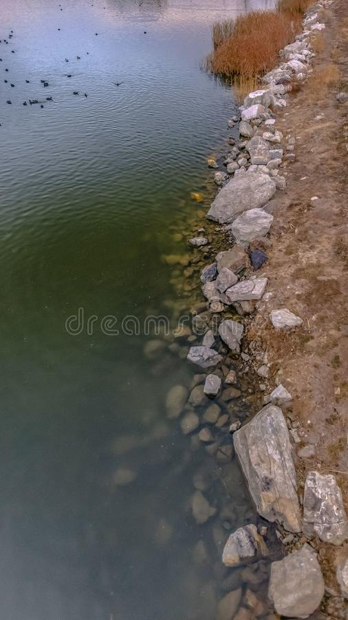 有排行岸和一座被成拱形的桥梁在它发光的水的岩石的清楚的垂直的湖 库存照片