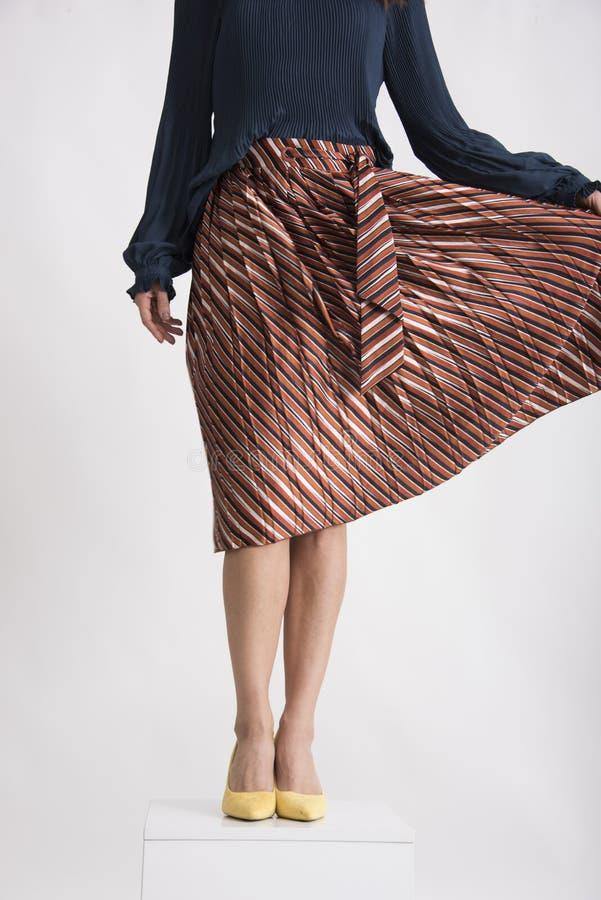 有掠过的裙子和黄色高跟鞋的时髦妇女的腿 免版税库存图片