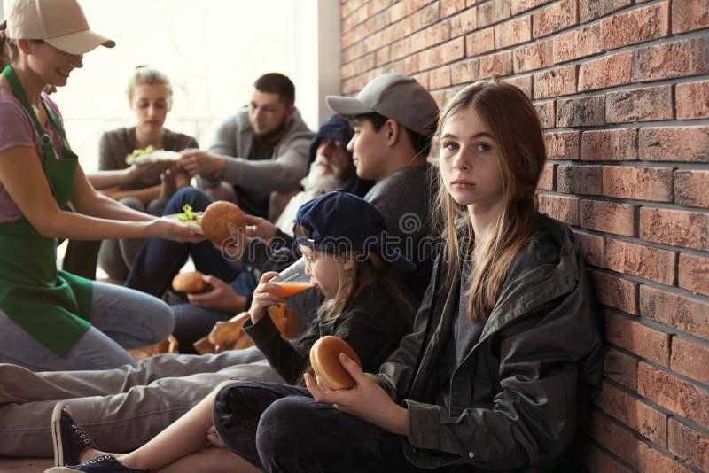 有接受食物的其他可怜的人的十几岁的女孩从志愿者 免版税库存照片