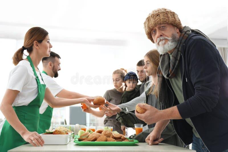 有接受食物的其他可怜的人的老人从志愿者 免版税库存图片